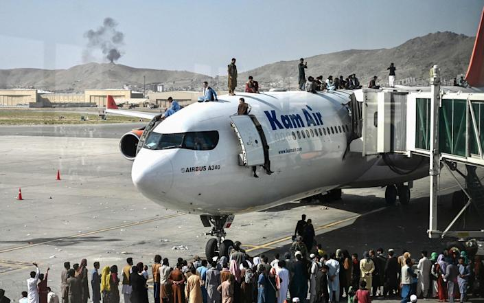 Afghan people climb atop a plane as they wait at the Kabul airport on Monday - Wakil Kohsar
