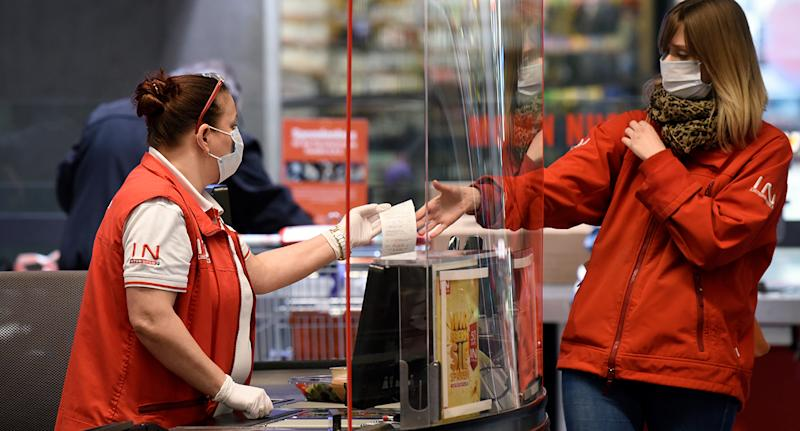 Supermarket staff wearing gloves and a face mask hands a receipt to a shopper also wearing a mask in Austria.