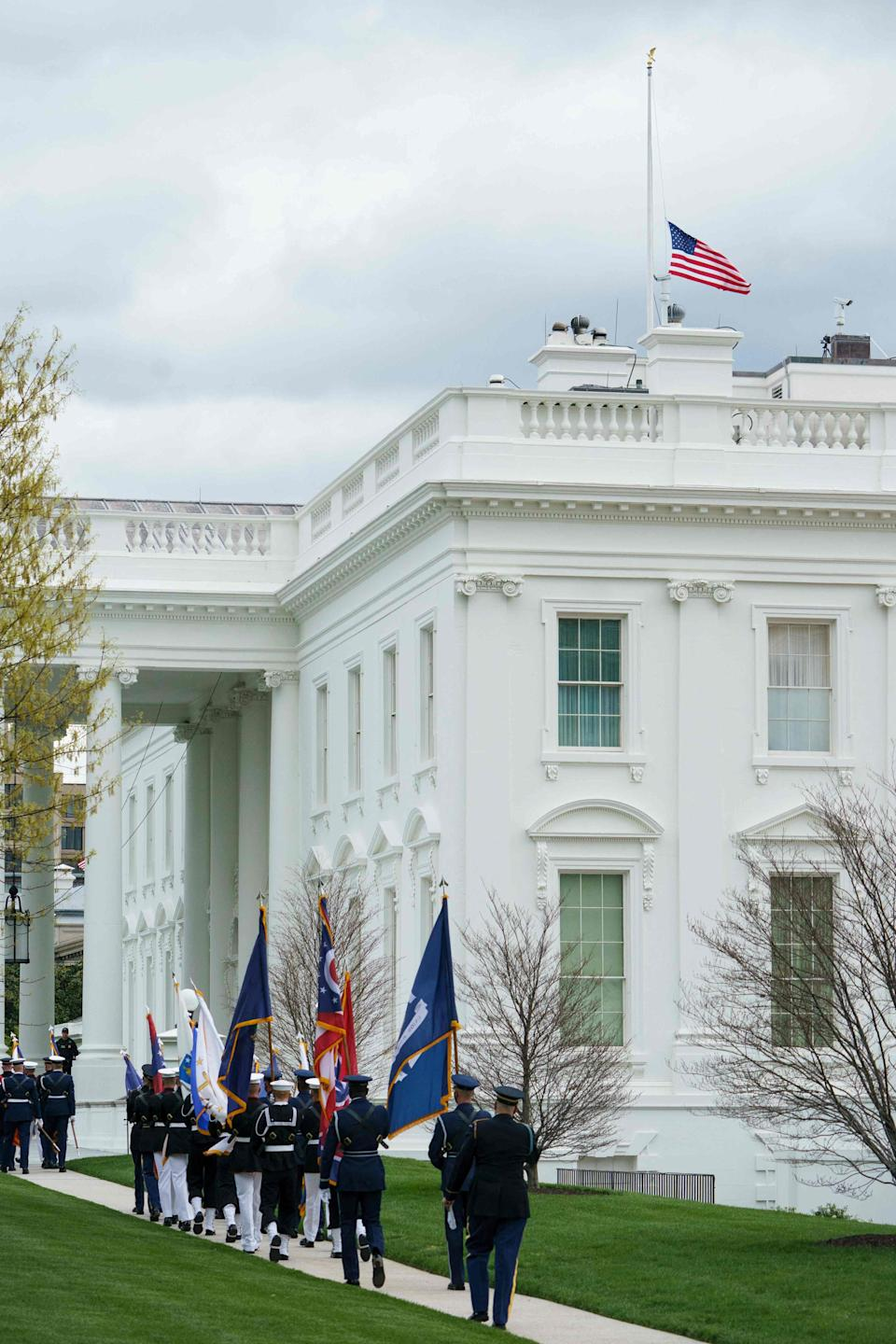 The flag above the White House flies at half staff in honor of the Indianapolis, Indiana shooting victims, in Washington, DC on April 16, 2021 as an honor guard setting up for the arrival for Japan's Prime Minister Yoshihide Suga is seen walking by.