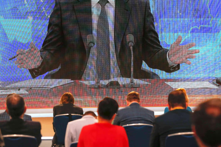 Journalists listen to Russian President Vladimir Putin speaking via video call during his news conference in Moscow, Russia, Thursday, Dec. 17, 2020. This year, Putin attended his annual news conference online due to the coronavirus pandemic. (AP Photo/Alexander Zemlianichenko)