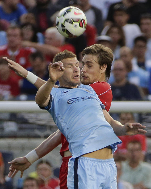 Manchester City forward Edin Dzeko, left, goes up for a header against Liverpool forward Samed Yesil in the first half of a Guinness International Champions Cup soccer tournament match, Wednesday, July 30, 2014, at Yankee Stadium in New York. (AP Photo/Julie Jacobson)