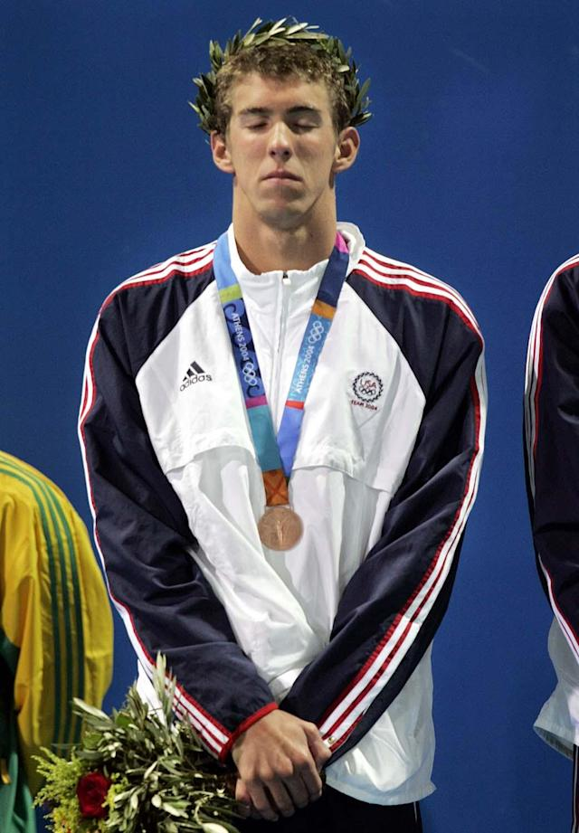 Michael Phelps of the U.S. reacts on the medal stand after the U.S. finished third in the 4x100m freestyle relay at the 2004 Olympic Games Sunday, Aug. 15, 2004 in Athens, Greece. (AP Photo/Mark Baker)