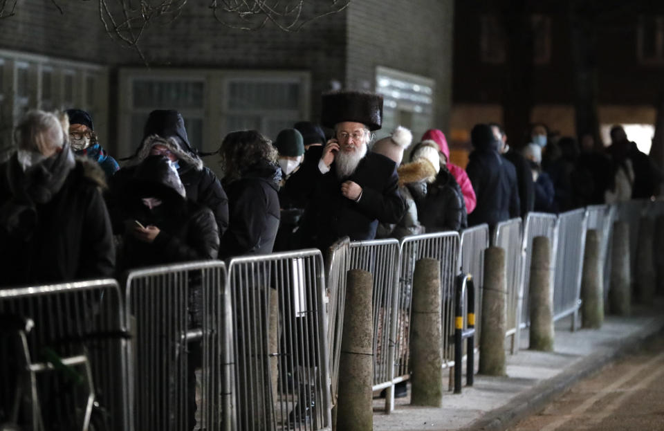 A man from the Haredi Orthodox Jewish community, center, queues outside an event to encourage vaccine uptake in Britain's Haredi community at the John Scott Vaccination Centre in London, Saturday, Feb. 13, 2021. The event aims to breakdown some of the misconceptions about vaccines, as well as myths and negative publicity surrounding the Haredi community which has been hard hit during the COVID-19 pandemic. (AP Photo/Frank Augstein)