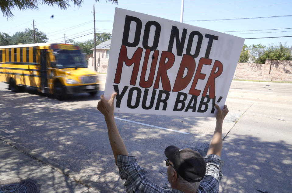 David Trujillo holds a sign as a school bus drives by on the street in front of a building housing an abortion provider in Dallas, Thursday, Oct. 7, 2021. A federal judge has ordered Texas to suspend a new law that has banned most abortions in the state since September. The order Wednesday by U.S. District Judge Robert Pitman freezes for now the strict abortion law known as Senate Bill 8. (AP Photo/LM Otero)