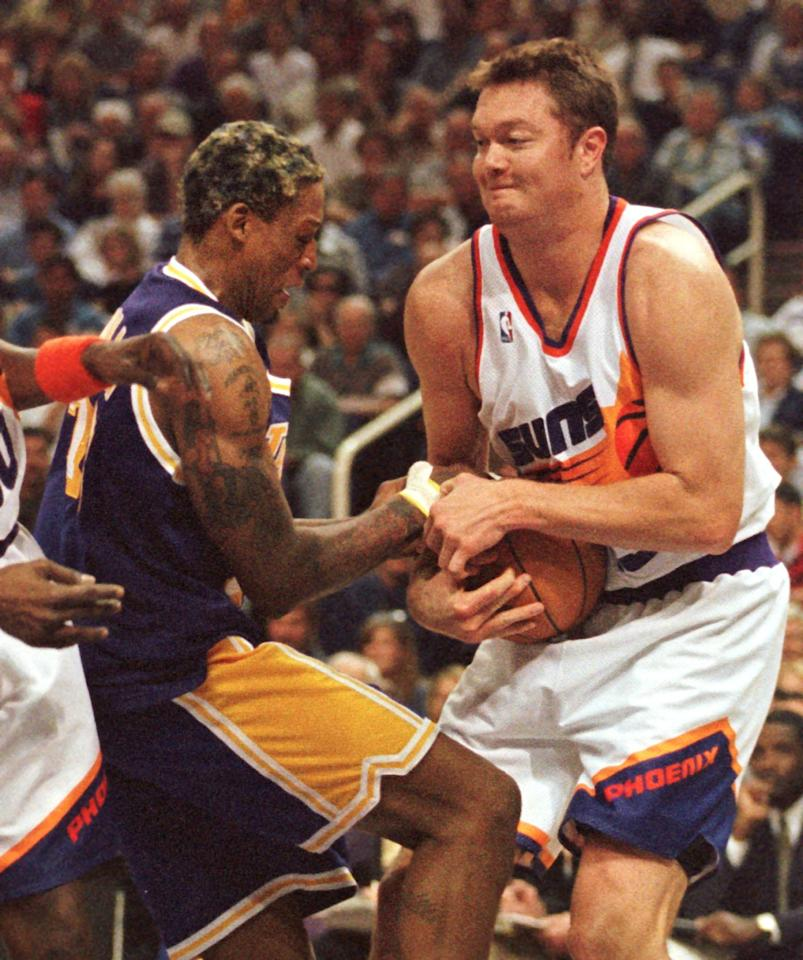 PHOENIX, AZ - MARCH 1:  Los Angeles Lakers forward Dennis Rodman and Phoenix Suns center Luc Longley battle for possession during the second quarter 01 March at America West Arena in Phoenix,AZ.  Rodman and Longley were members of last year's Chicago Bulls. The Lakers won 97-91.  (Photo credit should read MIKE FIALA/AFP via Getty Images)