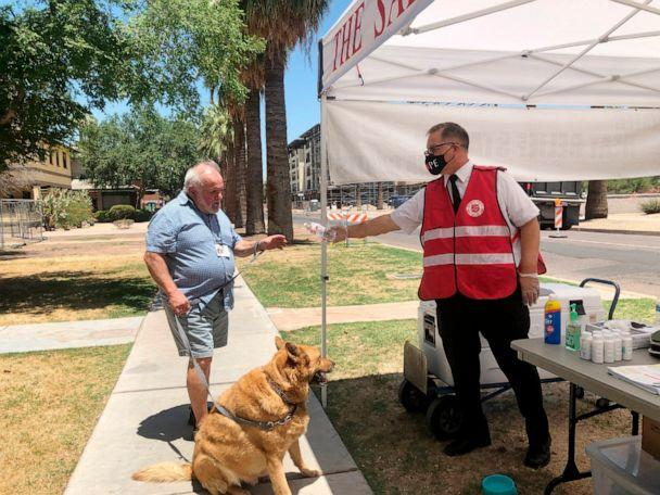 PHOTO: Salvation Army Maj. David Yardley offers water to a passerby at a heat relief station offering cold water and a cool place to rest out of the heat in Phoenix, May 28, 2020. (Anita Snow/AP, FILE)