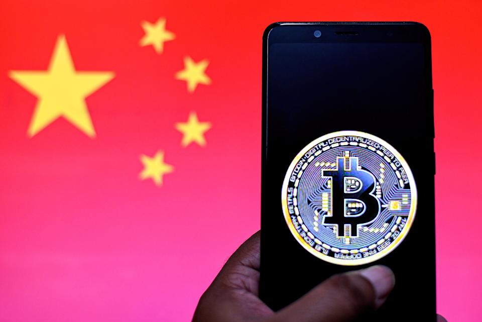 INDIA - 2021/09/20: In this Photo illustration a Bitcoin logo seen displayed on a smartphone with a China flag in the background. (Photo Illustration by Avishek Das/SOPA Images/LightRocket via Getty Images)