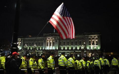 A supporter of Donald Trump waves the US flag outside Buckingham Palace  - Credit: Alberto Pezzali /AP