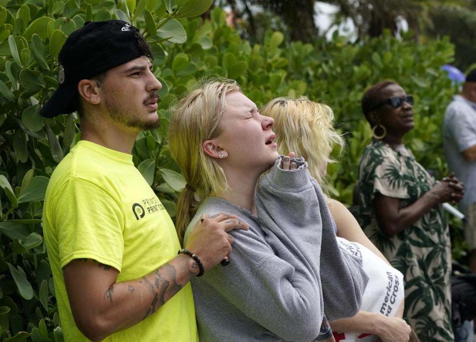 ADDS NAME OF HEVIA'S MOTHER AND THAT SHE DIED IN THE COLLAPSE - Ariana Hevia, of New Orleans, center, stands with Sean Wilt, left, on Friday, June 25, 2021, near the 12-story beachfront condo building that collapsed on Thursday in Surfside, Fla., north of Miami. Hevia's mother, Cassondra Billedeau-Stratton, lived in the building and is listed among those who died in the collapse. (AP Photo/Lynne Sladky)