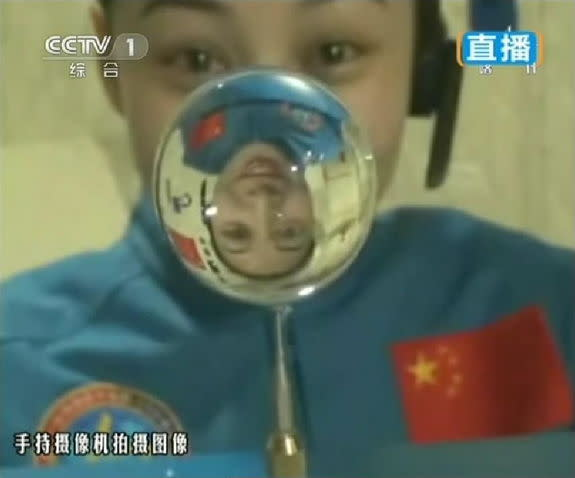 This screengrab from television taken on June 20, 2013 shows female astronaut Wang Yaping, one of the three crew members of Shenzhou-10 spacecraft, making a water ball in space during a lecture to students on Earth, aboard China's space module