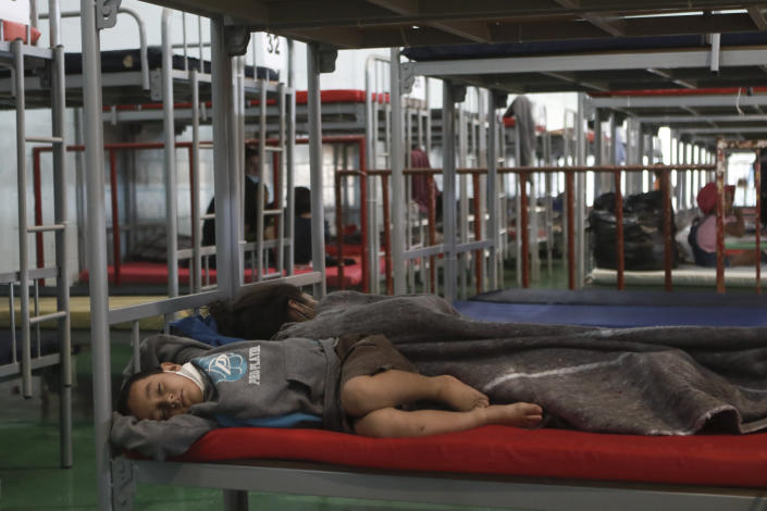 A mother and child sleep in a cot at the Kiki Romero Sports Complex after they were deported from the U.S., in Ciudad Juarez, Mexico, Wednesday, April 21, 2021. Mexico said it is planning to set up 17 shelters for underage migrants along the country's southern border, as well as some along the northern border with the United States, amid a wave of child migrants coming from Central America. (AP Photo/Christian Chavez)