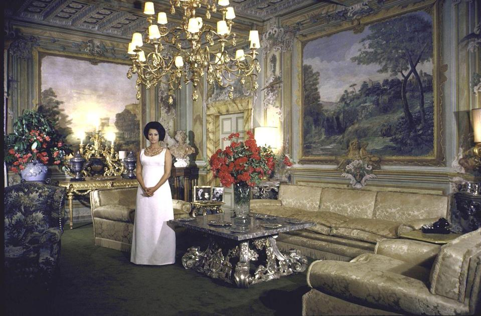 <p>The house was fitted with magnificent paintings, gilded ceilings and luxurious fabrics. Sophia was known to entertain often at the estate. Here, she's in the main living room in a white evening gown. </p>