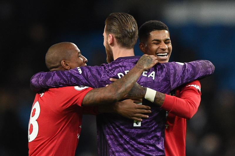 (L-R) Manchester United's English defender Ashley Young, Manchester United's Spanish goalkeeper David de Gea and Manchester United's English striker Marcus Rashford celebrate victory at the end of the English Premier League football match between Manchester City and Manchester United at the Etihad Stadium in Manchester, north west England, on December 7, 2019. (Photo by Oli SCARFF / AFP) / RESTRICTED TO EDITORIAL USE. No use with unauthorized audio, video, data, fixture lists, club/league logos or 'live' services. Online in-match use limited to 120 images. An additional 40 images may be used in extra time. No video emulation. Social media in-match use limited to 120 images. An additional 40 images may be used in extra time. No use in betting publications, games or single club/league/player publications. / (Photo by OLI SCARFF/AFP via Getty Images)