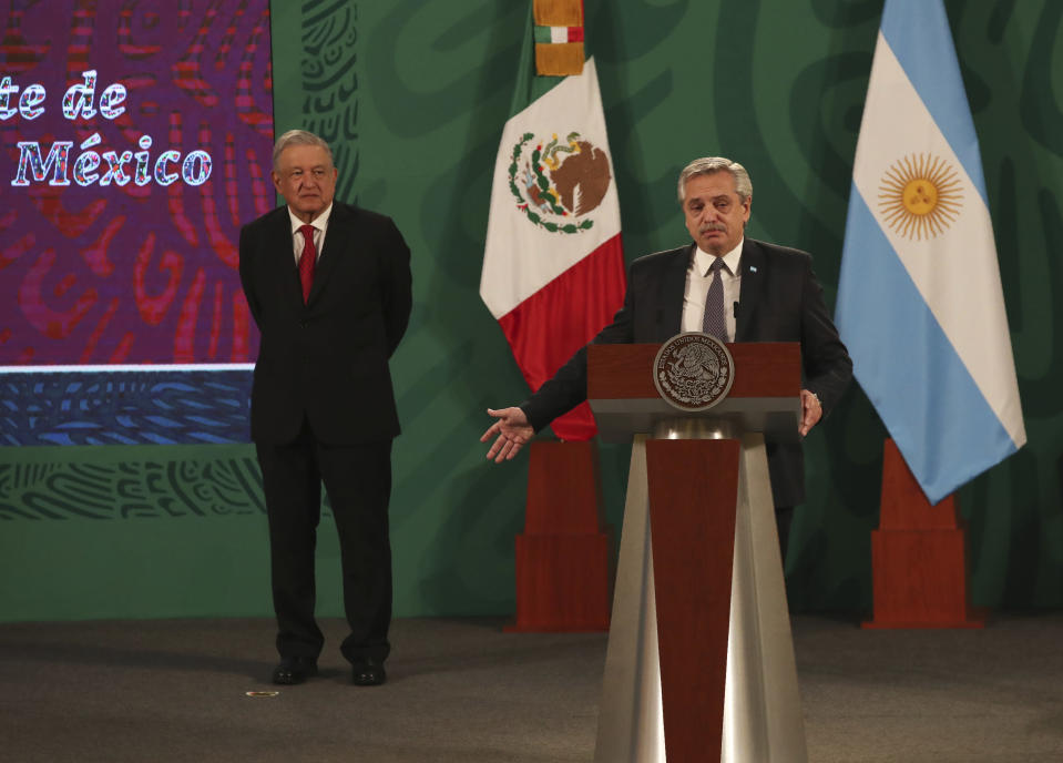 Argentina's President Alberto Fernández speaks during Mexican President Andrés Manuel López Obrador's daily, morning press conference, as Lopez Obrador stands behind at the National Palace in Mexico City, Tuesday, Feb. 23, 2021. Fernández is on a four-day official visit to Mexico. (AP Photo/Marco Ugarte)