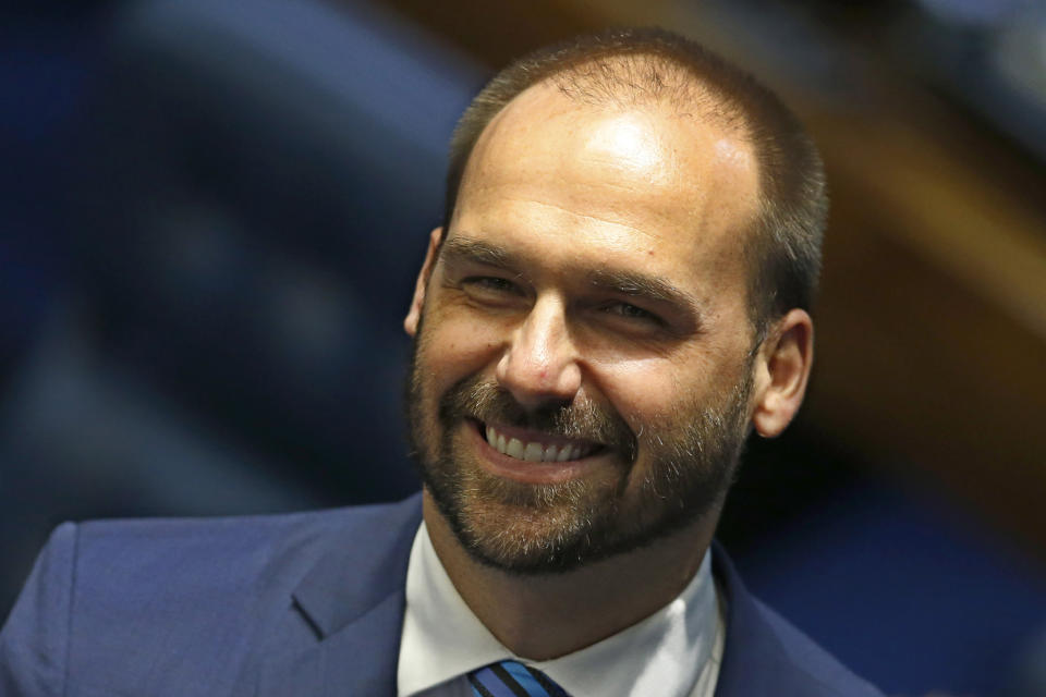 FILE - In this Oct. 22, 2019 file photo, lawmaker Eduardo Bolsonaro, son of the nation's president, smiles during the final voting session on pension reform at the Senate in Brasilia, Brazil. Eduardo Bolsonaro said Thursday, October 31, 2019, that the Brazilian government should adopt the military dictatorship's tactics to control an eventual radicalization of any protests. (AP Photo/Eraldo Peres, File)