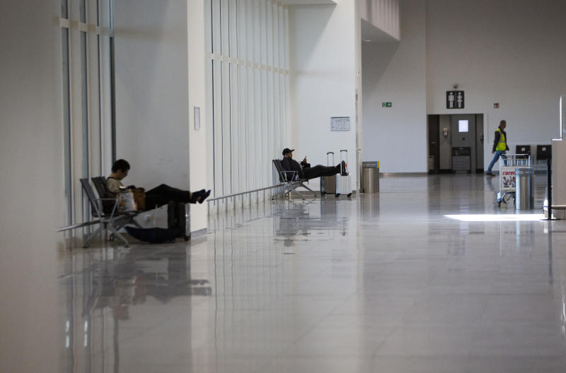 Two people sit at a distance from each other in the main terminal of Brussels International Airport in Brussels, Thursday, March 12, 2020. The European Union has slammed the new anti-virus travel ban announced by U.S. President Donald Trump on Wednesday. For most people, the new coronavirus causes only mild or moderate symptoms, such as fever and cough. For some, especially older adults and people with existing health problems, it can cause more severe illness, including pneumonia.(AP Photo/Virginia Mayo)