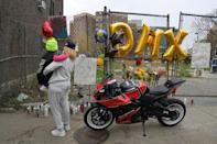 A fan pays her respects at a makeshift memorial for hip-hop star DMX outside White Plains hospital north of New York City