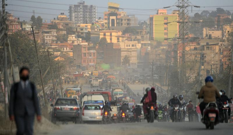 Vehicles and motorbike riders travel on a dusty road in Kathmandu (AFP Photo/PRAKASH MATHEMA)