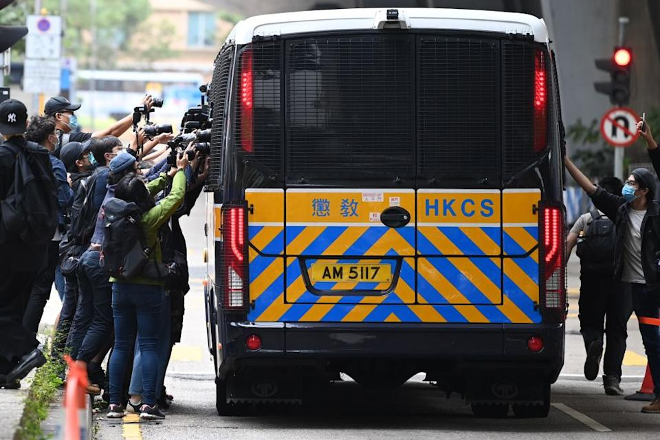 """Members of the media surround a correctional services bus purportedly carrying pro-democracy activists Agnes Chow, Ivan Lam and Joshua Wong as it leaves court in Hong Kong on November 23, 2020.span class=""""copyright""""PETER PARKS/AFP via Getty Images/span"""