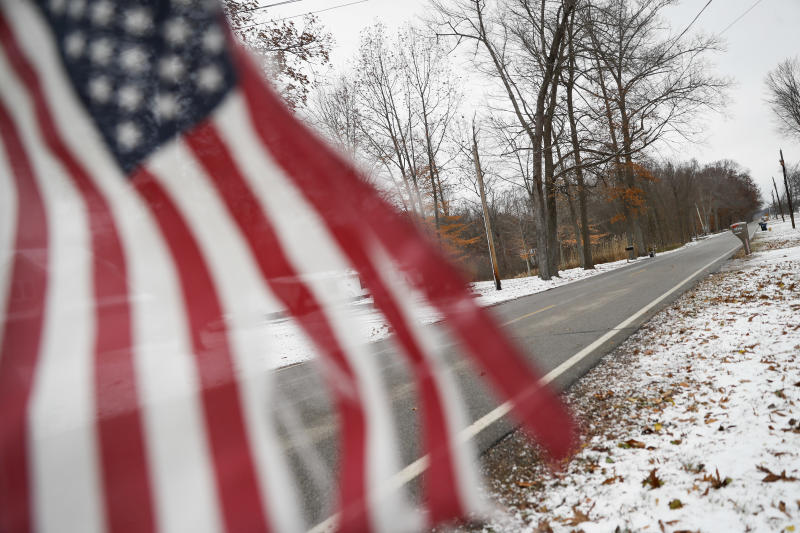 FILE - In this Nov. 28, 2018, file photo, snow blankets the front yards of homes as a flag is flown from a mailbox along Lyntz Townline Rd in Warren, Ohio. An economic renaissance in the industrial Midwest promised by President Donald Trump has suffered in recent weeks in ways that could be problematic for Trump's 2020 re-election. (AP Photo/John Minchillo, File)