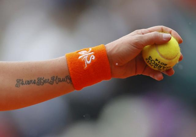 A tattoo is seen on the arm of Svetlana Kuznetsova of Russia as she prepares to serve to Simona Halep of Romania during their women's quarter-final match at French Open tennis tournament at the Roland Garros stadium in Paris June 4, 2014. REUTERS/Gonzalo Fuentes (FRANCE - Tags: SPORT TENNIS)