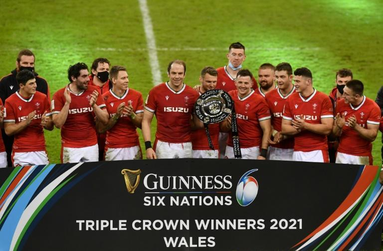 Triple joy - Wales captain Alun Wyn Jones (C) and fly-half Dan Biggar (centre right) hold the Triple Crown trophy after a 40-24 win over England