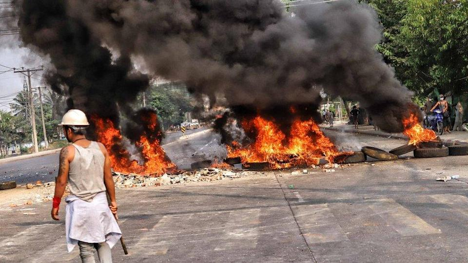 People clash with security forces as they continue to protest against the military coup and detention of elected government members in Hlaing Tharyar, Yangon