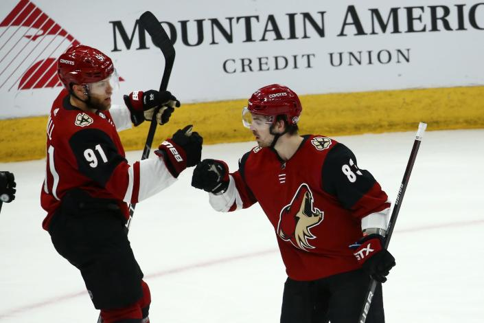 Arizona Coyotes left wing Taylor Hall (91) celebrates his goal against the San Jose Sharks with Coyotes right wing Conor Garland (83) during the second period of an NHL hockey game Tuesday, Jan. 14, 2020, in Glendale, Ariz. (AP Photo/Ross D. Franklin)