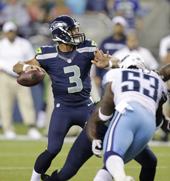 Seattle Seahawks quarterback Russell Wilson (3) throws a touchdown pass as Tennessee Titans linebacker Zac Diles (52) puts on defensive pressure in the second half of an NFL football preseason game, Saturday, Aug. 11, 2012, in Seattle. (AP Photo/Rick Bowmer)