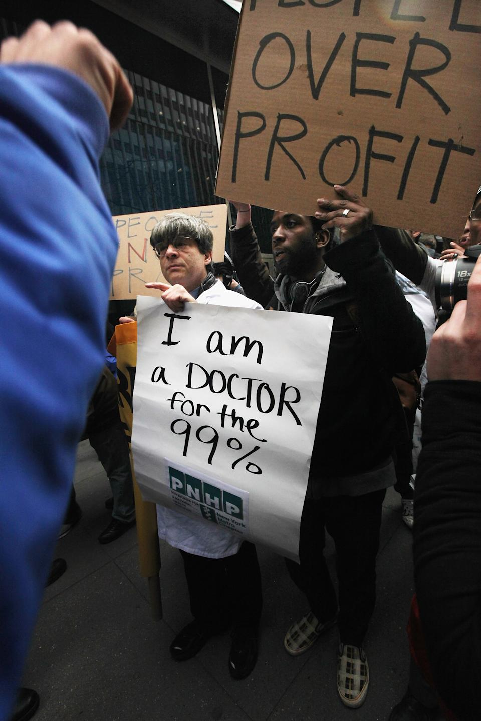 "NEW YORK, NY - FEBRUARY 29: A doctor points toward a police officer during an Occupy Wall Street ""Shut Down the Corporations"" protest in front of Pfizer headquarters on February 29, 2012 in New York City. Occupy movements across the country are planning protests in dozens of cities against corporate power. (Photo by Mario Tama/Getty Images)"