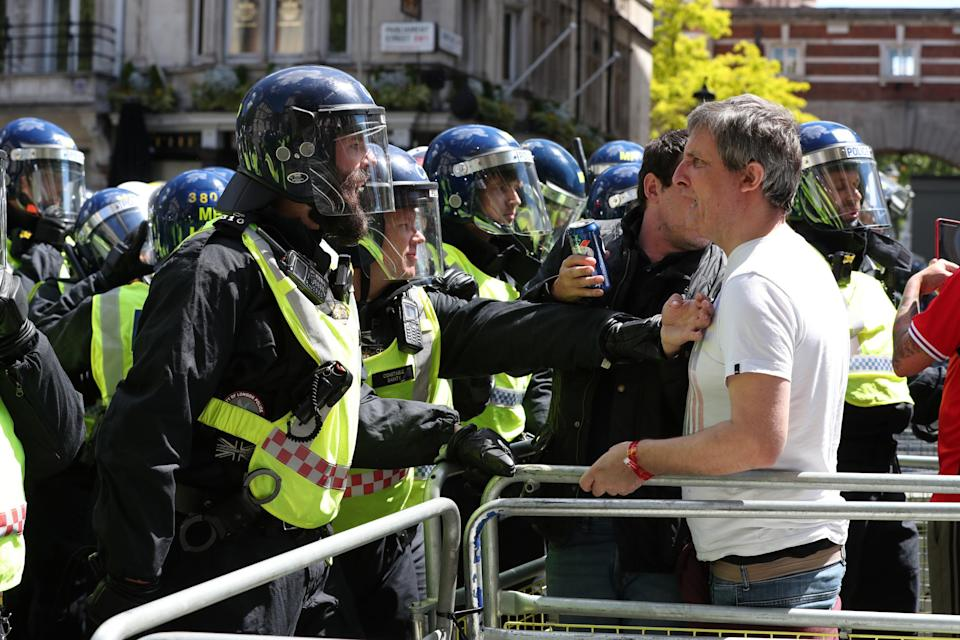 A protester confronts police officers in central London (PA)
