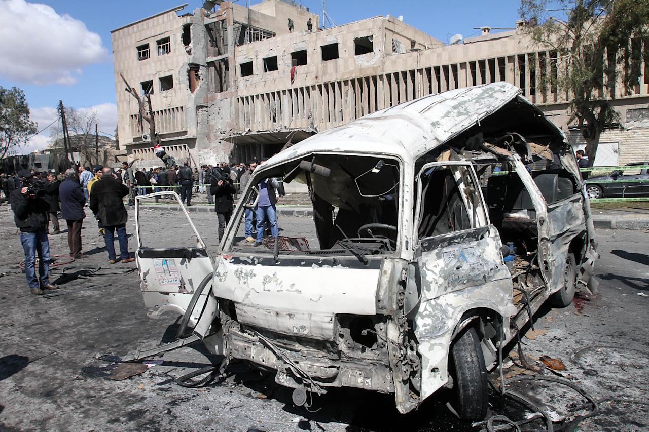 A destroyed van is seen in front the damaged building of the Syrian criminal security department, which was attacked by one of two explosions, in Damascus, Syria, on Saturday, March 17, 2012. Twin bombings struck government targets in the Syrian capital early Saturday, killing security forces and civilians and leaving pools of blood and carnage in the streets, according to state-run television. (AP Photo/Bassem Tellawi)