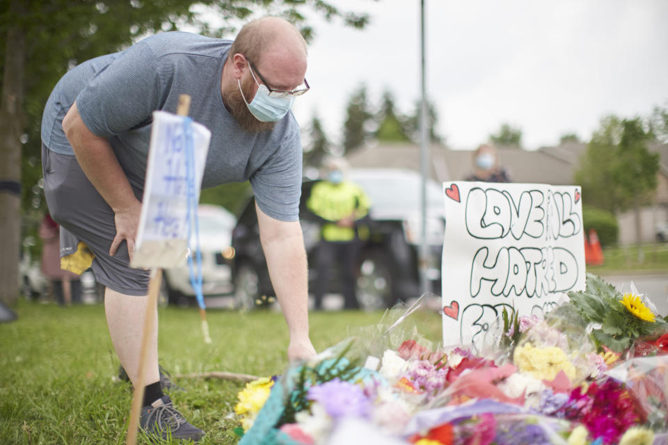 <p>A man places flowers at the scene of a hate-motivated vehicle attack in London, Ont. on Tuesday, June 8, 2021, which left four members of a family dead and sent one to hospital on Sunday evening. THE CANADIAN PRESS/ Geoff Robins</p>