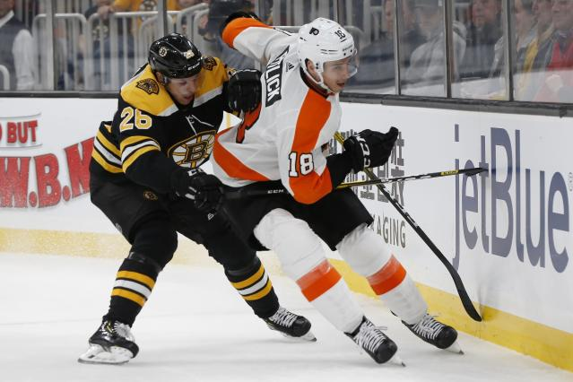 Boston Bruins' Par Lindholm (26) and Philadelphia Flyers' Tyler Pitlick (18) battle along the boards during the first period of an NHL hockey game in Boston, Sunday, Nov. 10, 2019. (AP Photo/Michael Dwyer)