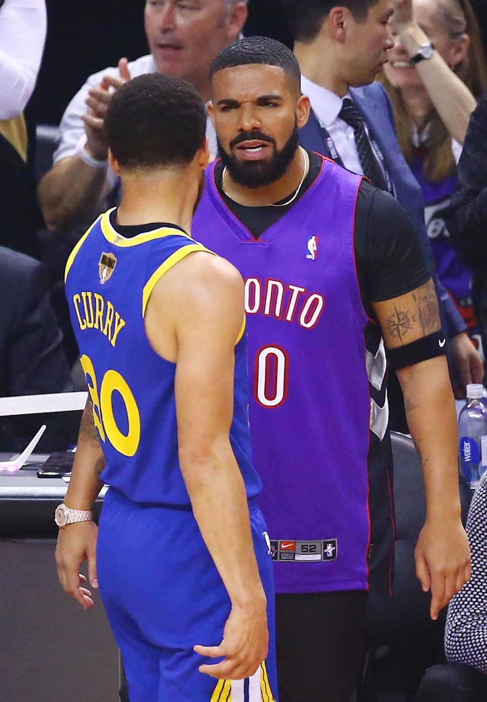 Rapper Drake and Stephen Curry #30 of the Golden State Warriors exchange words during a timeout in the first quarter during Game One of the 2019 NBA Finals between the Golden State Warriors and the Toronto Raptors at Scotiabank Arena on May 30, 2019 in Toronto, Canada. (Photo by Vaughn Ridley/Getty Images)