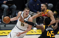 Denver Nuggets center Nikola Jokic, left, drives to the basket as Utah Jazz guard Donovan Mitchell, front right, and center Rudy Gobert defend in the second half of an NBA basketball game Sunday, Jan. 31, 2021, in Denver. (AP Photo/David Zalubowski)