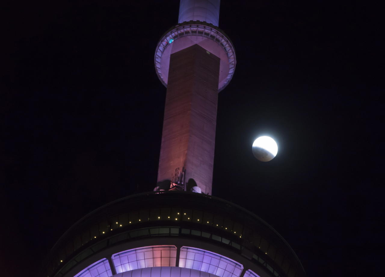 <p>An eclipse of the moon progresses behind the CN Tower in Toronto on Sunday, Jan. 20, 2019. (Frank Gunn/The Canadian Press via AP) </p>