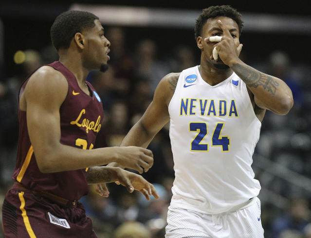 Nevada forward Jordan Caroline (24) reacts to hitting a 3-pointer against Loyola-Chicago forward Aundre Jackson during the first half of an NCAA men's college basketball tournament regional semifinal Thursday, March 22, 2018, in Atlanta. (Curtis Compton/Atlanta Journal-Constitution via AP)