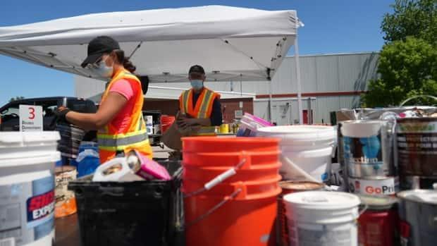 Workers wear masks while operating a drop-off clinic for toxic and non-recyclable waste in the Aylmer district of Gatineau, Que., on May 29, 2021. (Felix Desroches/Radio-Canada - image credit)