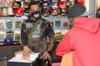 <p>T.I. spreads holiday cheer by gifting a student from Next Level Boys Academy clothes and shoes during Harris Community Works Holiday Caravan at DLTR on Monday in Atlanta.</p>