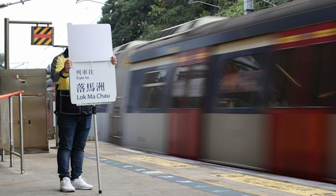 An MTR worker uses a board to display a train's destination, because display screens still have not been fixed. Photo: Winson Wong