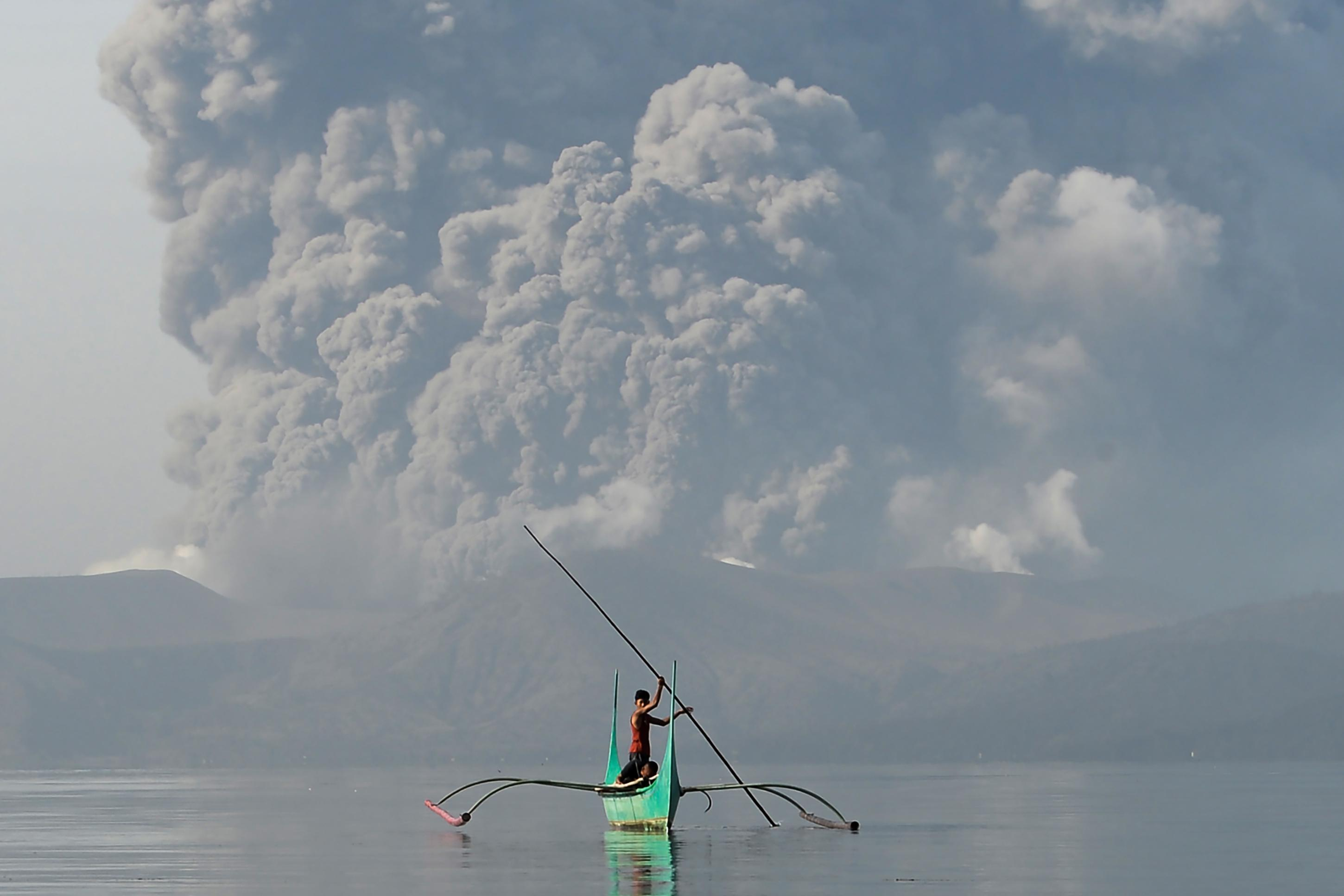 "TOPSHOT - A youth living at the foot of Taal volcano rides an outrigger canoe while the volcano spews ash as seen from Tanauan town in Batangas province, south of Manila, on January 13, 2020. - The Philippines was on alert January 13 for the ""explosive eruption"" of a volcano south of Manila, which officials said could be imminent after a massive column of ash forced a halt to flights at the capital's main airport. (Photo by Ted ALJIBE / AFP) (Photo by TED ALJIBE/AFP via Getty Images)"