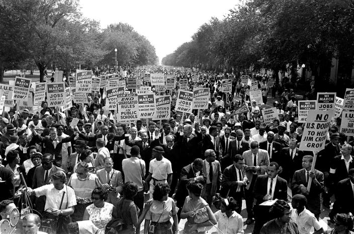 """FILE - In this Aug. 28, 1963, file photo Dr. Martin Luther King Jr., center left with arms raised, marches along Constitution Avenue with other civil rights protestors carrying placards, from the Washington Monument to the Lincoln Memorial during the March on Washington. The annual celebration of the Martin Luther King Jr. holiday in his hometown in Atlanta is calling for renewed dedication to nonviolence following a turbulent year. The slain civil rights leader's daughter, the Rev. Bernice King, said in an online church service Monday, Jan. 18, 2021, that physical violence and hateful speech are """"out of control"""" in the aftermath of a divisive election followed by a deadly siege on the U.S. Capitol in Washington by supporters of President Donald Trump. (AP Photo, File)"""