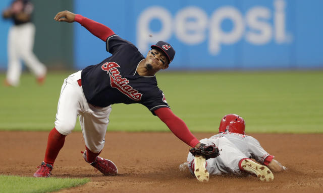 Cleveland Indians' Francisco Lindor, reaches but can't get to a ball thrown by catcher Yan Gomes as Cincinnati Reds' Billy Hamilton slides safely to second base on a steal in the seventh inning of a baseball game, Monday, July 9, 2018, in Cleveland. Hamilton advanced to third base on a throwing error by Gomes. (AP Photo/Tony Dejak)
