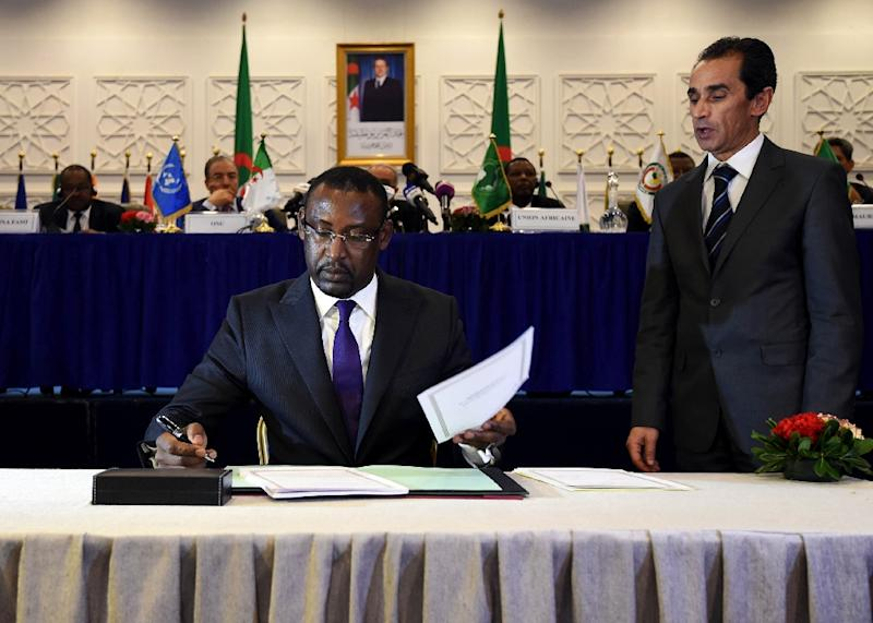 Malian Foreign Minister Abdoulaye Diop (C) is seen signing a peace agreement in 2015, as part of mediation talks between the Malian government and some northern armed groups in the Algerian capital Algiers (AFP Photo/FAROUK BATICHE)