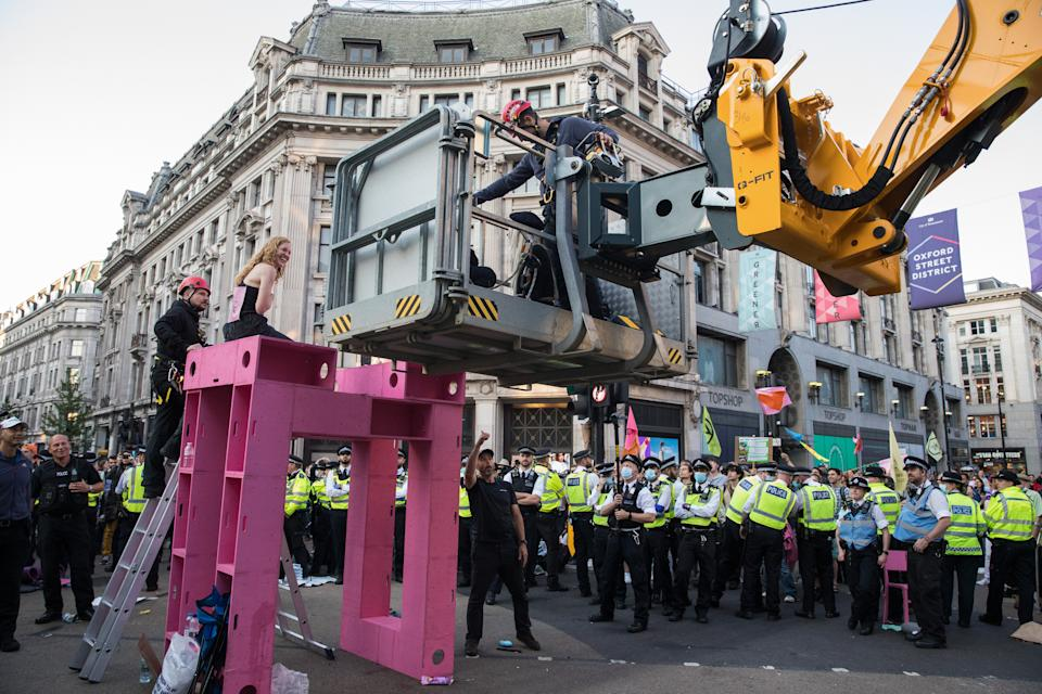 Police officers remove an Extinction Rebellion activist who had taken part in a pink roadblock of Oxford Circus by women and FINT-identifying environmental activists during the third day of Impossible Rebellion protests on 25th August 2021 in London, United Kingdom. Extinction Rebellion are calling on the UK government to cease all new fossil fuel investment with immediate effect. (photo by Mark Kerrison/In Pictures via Getty Images)