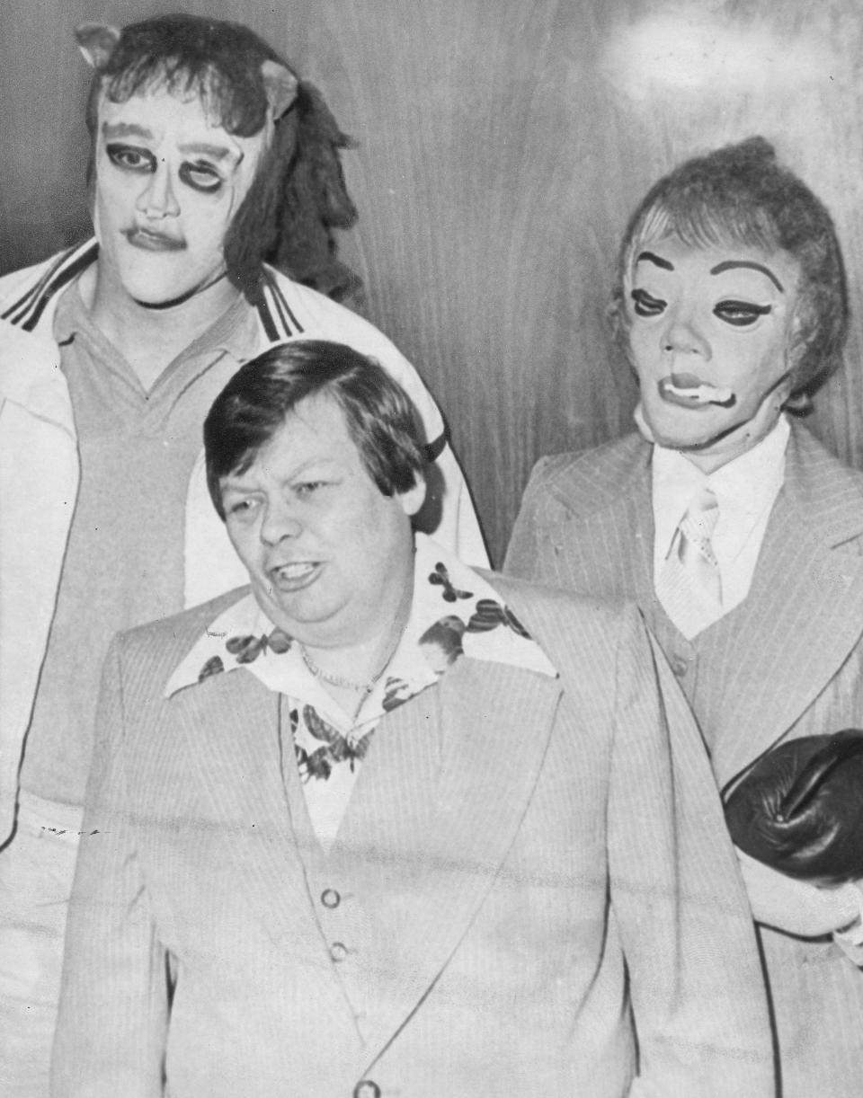 This 1979 photo shows transgender man Dante 'Tex' Gill, flanked by masked Frank Cocchiara, left, and Donna Potts while leaving the Public Safety Building in Pittsburgh, Pa. (Credit: Pittsburgh Post-Gazette via AP)