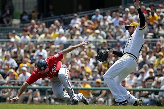 Pittsburgh Pirates first baseman Ike Davis, right, and Washington Nationals' Anthony Rendon, left, collide during a rundown between first and second during the third inning of a baseball game in Pittsburgh Sunday, May 25, 2014. Rendon was awarded second base on the error by Davis. (AP Photo/Gene J. Puskar)