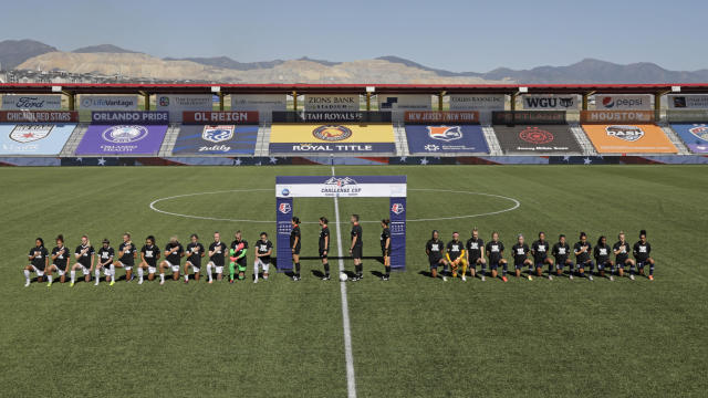 Players for the Portland Thorns, left, and the North Carolina Courage knell during the national anthem before the start of their NWSL Challenge Cup soccer match at Zions Bank Stadium Saturday, June 27, 2020, in Herriman, Utah. (AP Photo/Rick Bowmer)