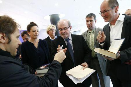 Author Rushdie signs autographs following opening news conference of the Frankfurt book fair